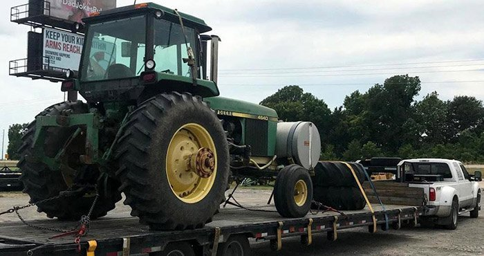 Green tractor on a trailer of a truck ready to be transported