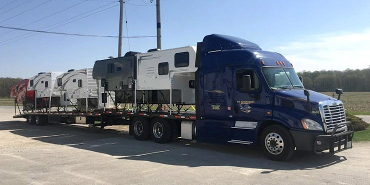 4 Rvs being transported for huge truck using open container trailer, Fifth wheel transportation California
