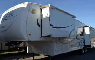 Huge white RV ready to be transported in a 5th Wheel camp
